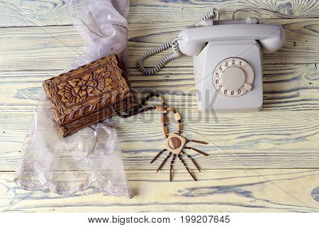 Women wooden necklace, casket and antique phone on a wooden table close-up