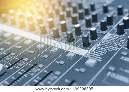 The mixer table or fader board for music production in light blue scene with the lighting effect