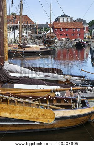 Traditional wooden fishing boats in the harbor of the village Spakenburg in the Netherlands. A historic shipyard in the background.