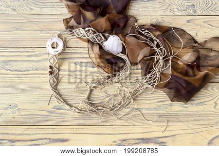 Beige, wicker belt (macrame) close-up on a wooden table