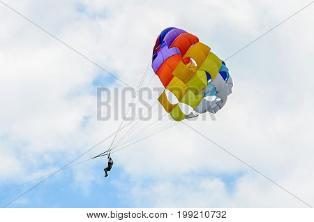Colored parasail wing in the blue clouds sky Parasailing also known as parascending or parakiting.
