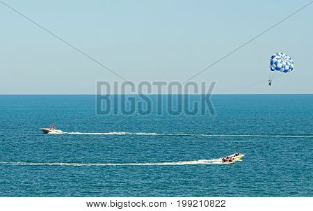 Blue Parasail Wing Pulled By A Boat In The Sea Water, Parasailing Also Known As Parascending Or Para