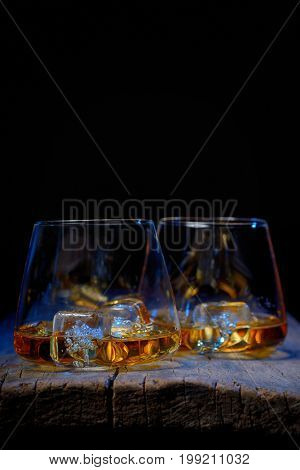 Glass of scotch whiskey and ice isolated on wooden table