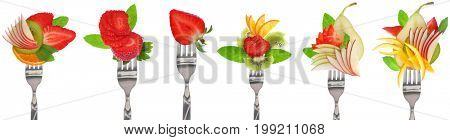 Fresh fruits slices on forks isolated on white background