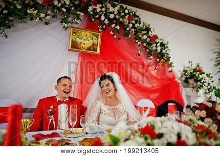 Gorgeous Wedding Couple Sitiing At The Table And Laughing On Theirr Wedding Day.