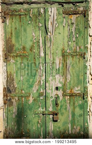 Aged old window blind with worn green paint