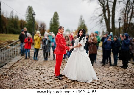 Gorgeous Wedding Couple Holding Hands On The Pavement While Crowd Of Kids Takes Pictures Of Them.