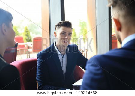 Happy smart business man with team mates discussing