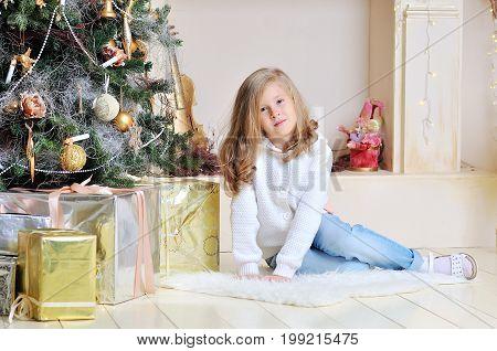 Happy little girl under the Christmas tree. Christmas interior.