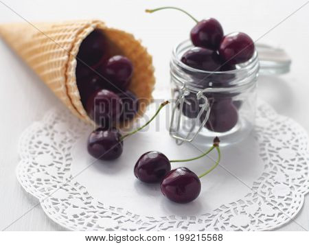 Fresh cherries in a wafer cornet and a jar lying upon white wooden table