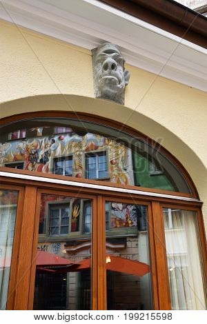 LUCERNE SWITZERLAND - JUNE 14 2017: Architectural detail on a street in the city of Lucerne Switzerland. Stone carved head and reflection of bright houses in windows glass