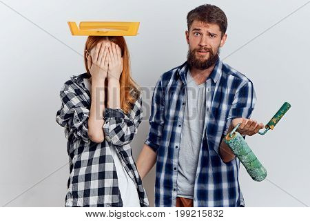 Man with a beard on a light background with a young woman holding construction tools for repair, emotions.
