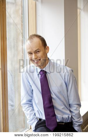 Nice handsome businessman standing in his office