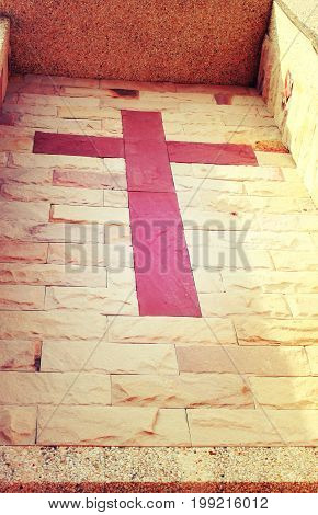 Red stone cross of christ built into brick wall vintage style process.