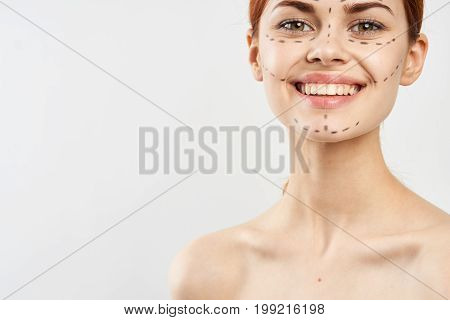 Young beautiful woman with contour for plastics on face on white isolated fn, smile, blank space for copy.
