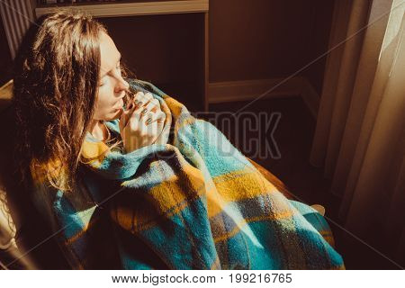 Winter cold concept. Young freezing woman in comfortable chair breathe warm air on frozen hands wrapped in warm fluffy woollen plaid blanket. Natural light. Warm atmosphere. Heating season. Cosy home