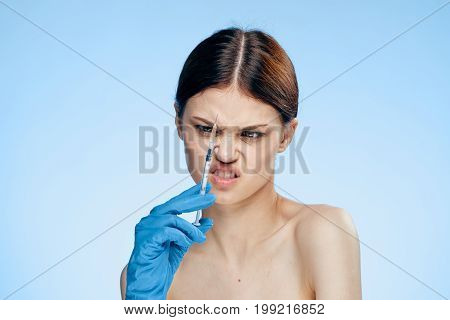 Young beautiful woman on a light blue background in gloves holds a syringe, portrait, emotions, medicine, plastic surgery.