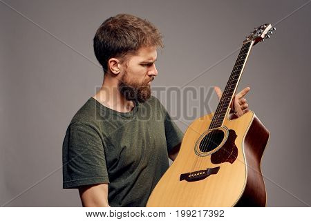 A man with a beard on a dark gray background holds a guitar, a musician, a musical instrument.