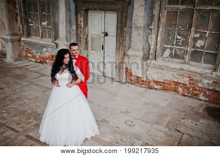Stunning Wedding Couple Posing Next To The Ancient Doors Of A Castle.