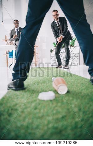 multiethnic group of businessmen playing mini golf in office