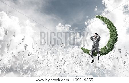 Frustrated businessman sitting on green moon and closing ears with hands