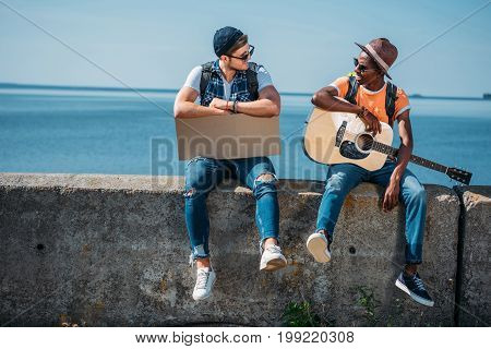 Multicultural Young Men With Cardboard And Guitar Resting On Parapet While Hitchhiking During Trip