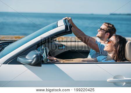 Multicultural Young Couple Riding Car At Seaside While Traveling Together