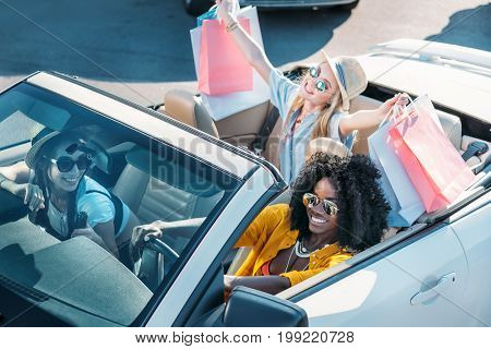 Multiethnic Young Women Riding Car After Shopping Together