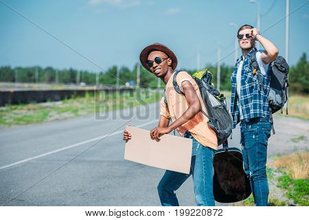 Multiethnic Young Men With Empty Cardboard Looking For Car While Hitchhiking During Trip