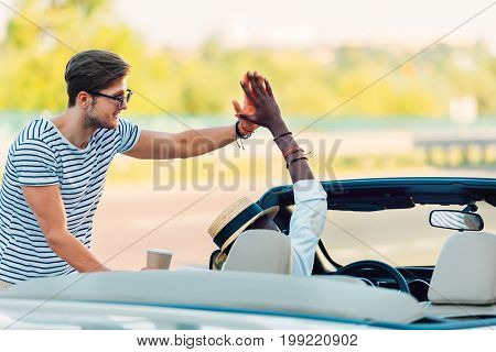 multicultural young men giving high five to each other while traveling together