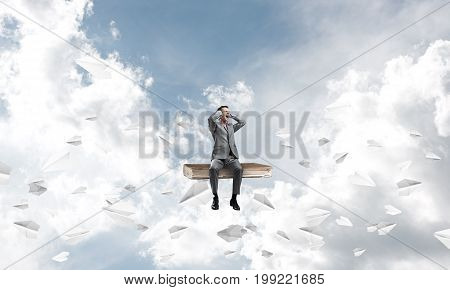 Frustrated businessman sitting on old book and closing ears with hands