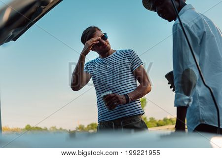 Multiethnic Friends With Coffee To Go Having Conversation Near Broken Car