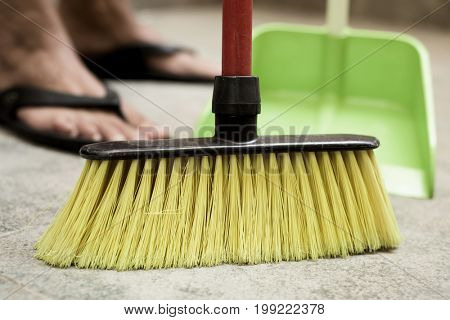 closeup of a young man sweeping the floor with a broom of green synthetic bristles and a green dustpan