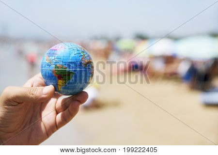 closeup of a young caucasian man with a world globe in his hand on a crowded beach, next to the seashore