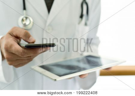 closeup of a young caucasian doctor man wearing a white coat using a smartphone while is checking a chest radiograph in a tablet computer