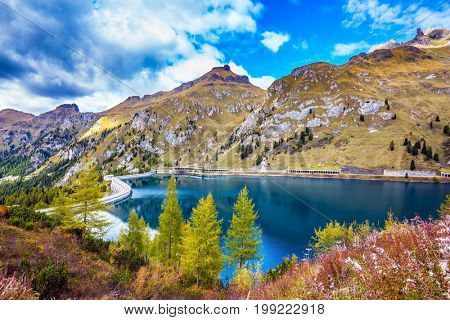 The concept of ecological and extreme tourism. The magic and harmony of the Dolomites. Mountain Lake Lago di Fedaia, Dolomites. Glacial lake with clear cold water