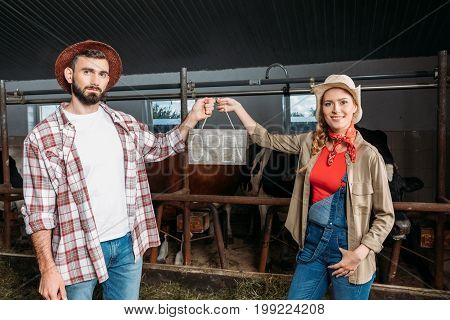 Farmers With Open Sign In Cowshed