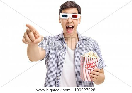 Joyful guy with a pair of 3D glasses and popcorn pointing at the camera and laughing isolated on white background