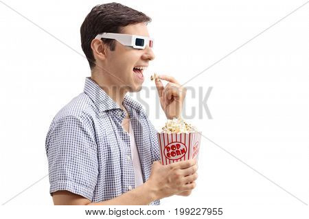 Profile shot of a young man wearing a pair of 3D glasses and eating popcorn isolated on white background