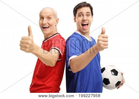 Young man and a senior with a football dressed in jerseys making thumb up signs isolated on white background