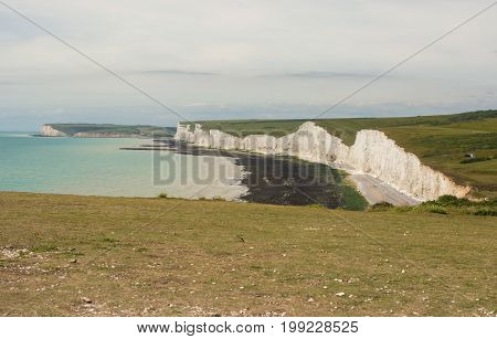 White chalk cliffs near to Beachy Head at Eastbourne East Sussex England. Seven Sisters cliffs and Seaford Head in distance with unrecognizable people.