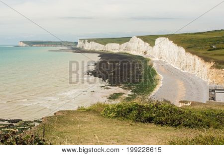 White chalk cliffs and shingle beach at Birling Gap near to Beachy Head at Eastbourne East Sussex England. Seven Sisters cliffs and Seaford Head in distance with unrecognizable people.