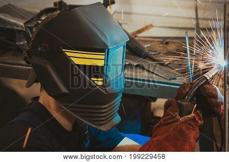 Male in face mask welds with argon-arc welding in body shop