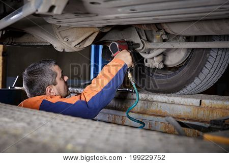 Mechanic Works on a Car. Repairs chassis