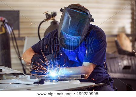 Male in face mask welds with argon-arc welding in body shop