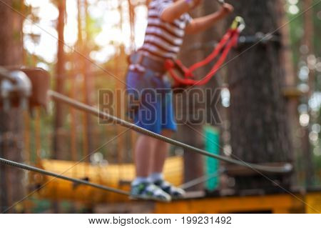 Adventure climbing in extreme rope park - child equipped with safety straps goes on hinged trail. 4 years old boy having activities outdoors.