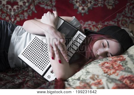A girl is sleeping with an old cassette tape recorder in her hands