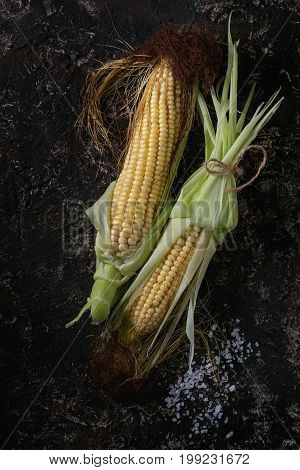 Young raw uncooked corn cobs in leaves ans sea salt. Top view over dark brown concrete texture background. Copy space