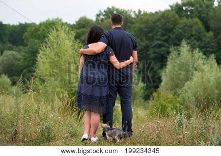 Couple In Love Embracing And Walking Outdoors Near The Forest With Yorkshire Terrier Dog, Back View.