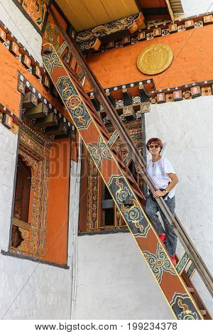Beautiful Caucasian woman standing on the exterior stairs in Druk Wangyal Lhakhang Temple Dochula Pass Bhutan.
